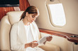 attractive businesswoman in suit using digital tablet in private plane