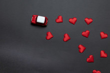 Top View Of A Little Children's Red Toy Car With Red Heart Shape On A Dark Black Background