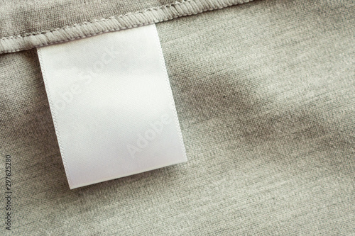 White blank laundry care clothing label on gray fabric texture background Wallpaper Mural