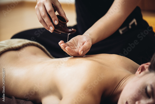 The massage therapist's hand spreads the body essential oil