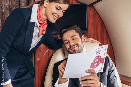Fotografie, Tablou handsome businessman and flight attendant in uniform looking at menu in private