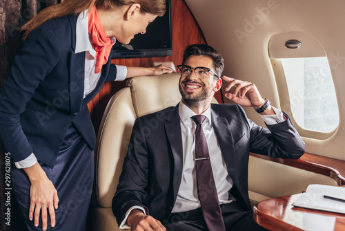 Foto smiling businessman in suit looking at flight attendant in private plane
