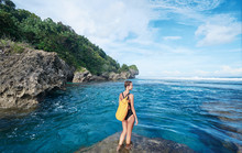 Tropical Traveling. Young Woman With Waterproof Backpack Walking By Low Tide Sea Beach.