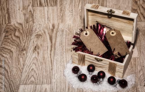 Imagen de Navidad con un fondo de madera, baúl  con espumillón rojo bolas rojas Fototapeta