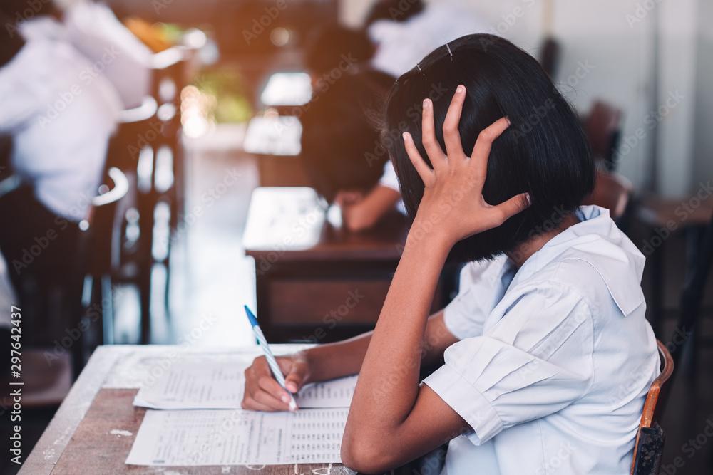 Fototapeta Students taking exam with stress in school classroom