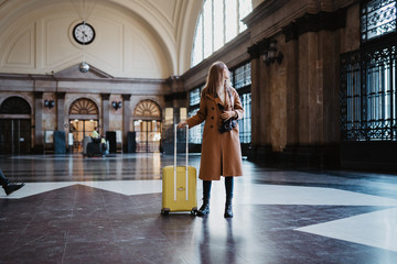 Tourist woman with suitcase retro camera on platform station in Barcelona. Girl traveler waiting train enjoy holiday weekend vacation in transport railway. Travel railroad station concept