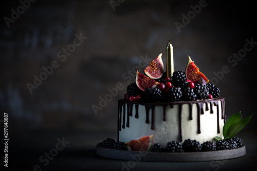 Fototapeta Cake decorated blackberries and figs with candle obraz