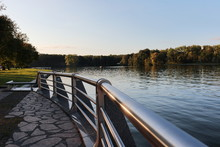 City Park In Minsk At Sunset. Tree On River Bank With Metal Constraction Bridge Pier, Nice Evening Mood