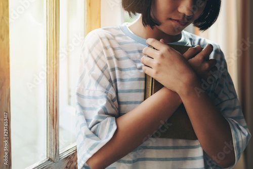 The girl hugged the holy scriptures Fototapeta