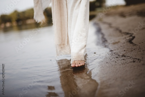 Photo Closeup shot of a female wearing a biblical robe walking on the shoreline with b