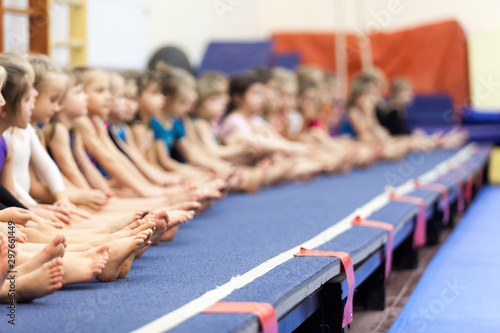 Gymnast girls sitting in line on gymnastic platform, unrecognizable children barefoot legs