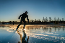 Sun At Sunset Is Shadowed By Silhouette Of One Skating Boy Close To Photographer, Another Boy Is Far Away. Two Teenage Boys Are Ice Skating On The Crystal Clear Frozen Lake In Northern Sweden
