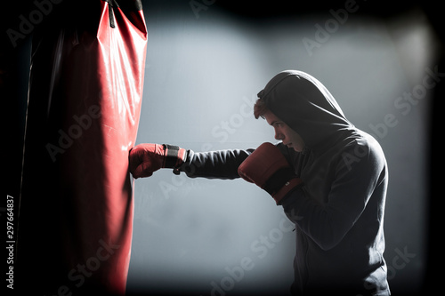 The young man workout a kick on the punching bag Фотошпалери