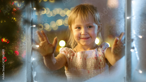 Foto auf AluDibond Logo On Christmas Eve Cute Little Girl Looks Through the Window and Smiles.
