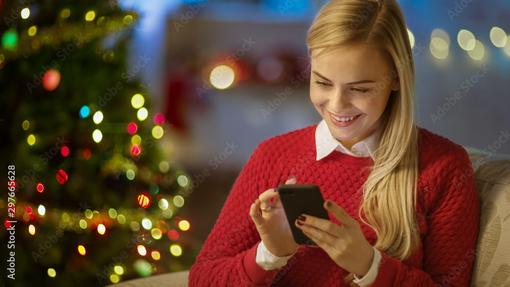 Fototapety, obrazy: Beautiful Blonde Woman Sits on a Couch and Uses Smartphone. Christmas Tree and Room Decorated with Lights are in the Background.