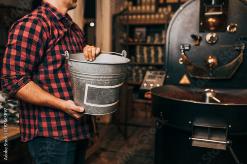 Man's hands holding freshly roasted aromatic coffee beans over a modern coffee roasting machine. - 297665897