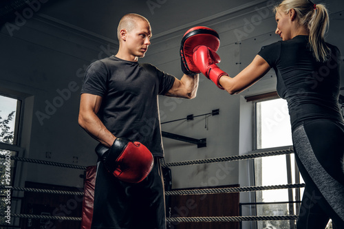 Fotografía Strong blond woman is trying to attack her coach while have boxing training