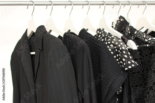 set of women's clothing in black in different colors on hangers, a concept for f Fotobehang