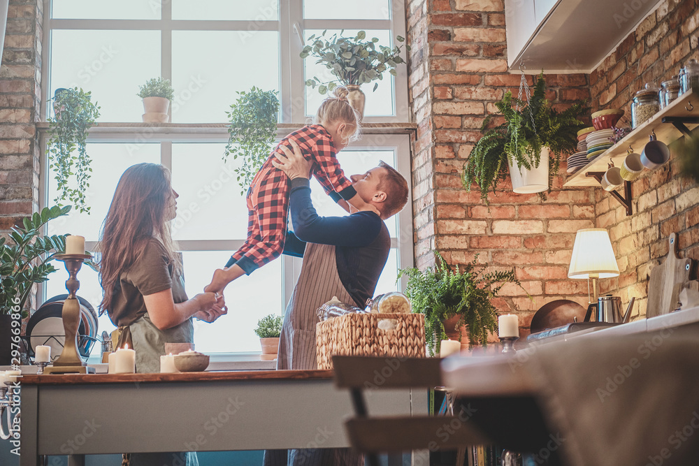 Fototapety, obrazy: Nice small family are together at the kitchen, they planning to cook something.