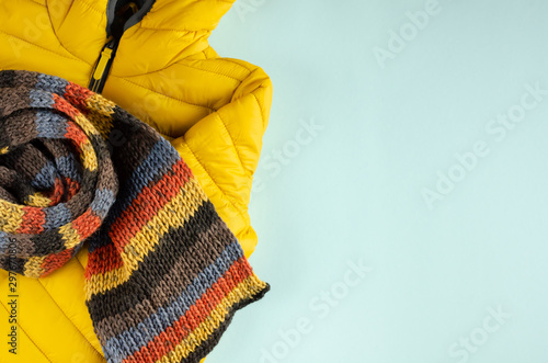 Papiers peints Glisse hiver Yellow kids winter jacket composition on blue background.