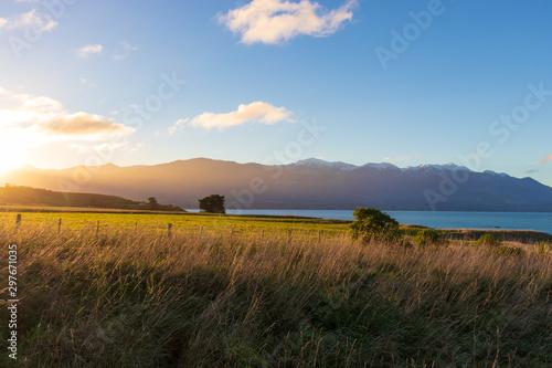 Foto auf AluDibond Grau Verkehrs Sunset over grass and mountains New Zealand