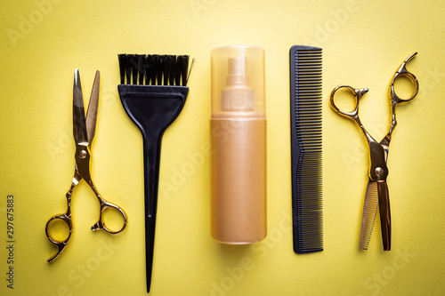 Various hair dresser and cut tools on yellow background with copy space