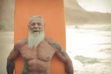 Senior Man With Orange Longboard. Happy Old Guy Having Fun Doing Extreme Sport. Joyful Elderly Concept - Image