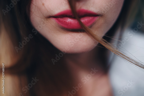 Close up portrait of part of caucasian woman face.  Thin woman lips with red lipstick on it. Concept of fashion and face.