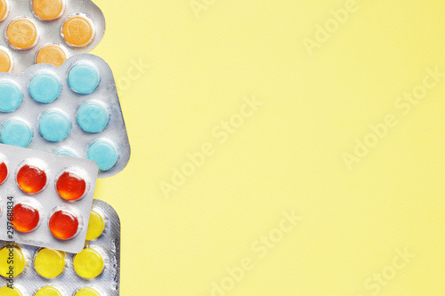 Lots of Blisters with color cough drops on yellow background Tablou Canvas