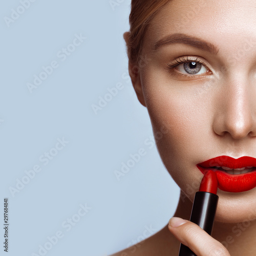 Obraz na plátně Beautiful girl with red lips and classic makeup with lipstick in hand