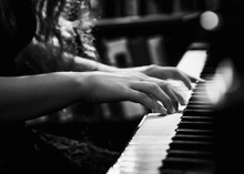 Black And White Photo Of Young Lady Playing The Piano