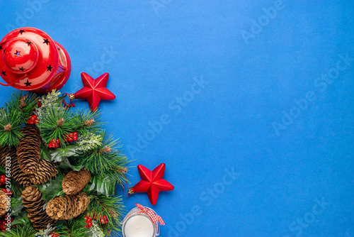 Christmas flat lay composition with fir branches decoration on blue surface.