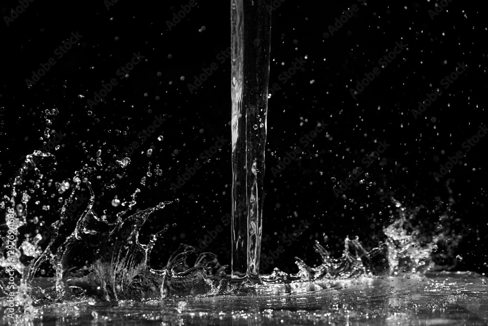 Fototapeta Water splash on black background. Jet and drops of clear liquid. Pouring transparent water