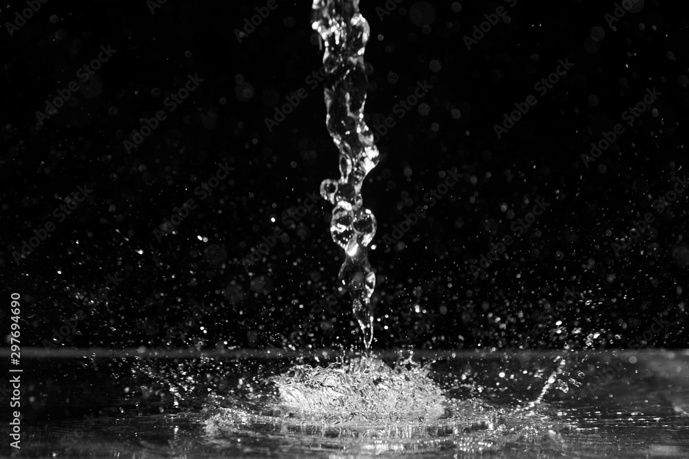 Fototapety, obrazy: Water splash on black background. Jet and drops of clear liquid. Pouring transparent water