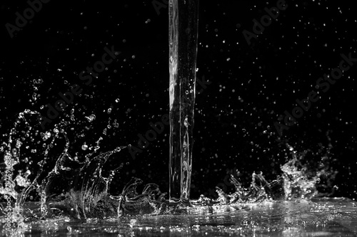 Water splash on black background. Jet and drops of clear liquid. Pouring transparent water