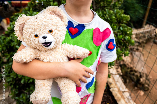 Fotografie, Obraz  Strange scene of boy with hearts t-shirt holding a dirty and old teddy bear