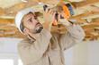 Leinwanddruck Bild - builder using cordless drill on wooden ceiling