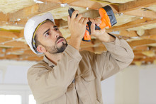 Builder Using Cordless Drill O...