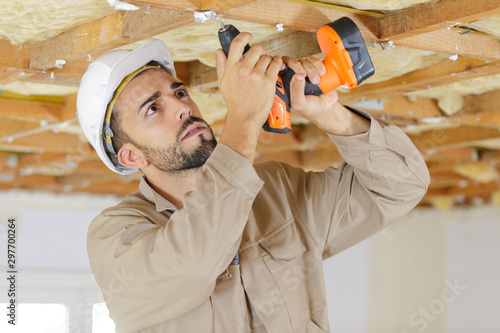 Obraz builder using cordless drill on wooden ceiling - fototapety do salonu