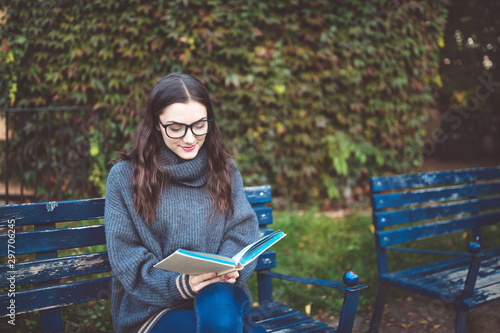 Valokuvatapetti Woman reading a book on the bench in a park