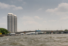Bangkok City, Thailand - March 17, 2019: Chao Phraya River. Gray Somdet Phra Pin Klao Bridge With Traffic Over Choppy Water Under Light Blue Cloudscape. Rattanakosin Skyscrapers On Left Bank.
