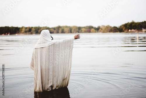 Cuadros en Lienzo Person wearing a biblical robe standing in the water with a hand up shot from be