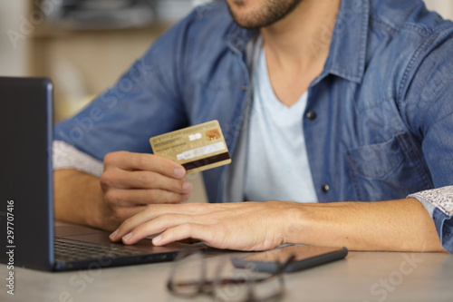 Photo  man paying with credit card on smart phone at home