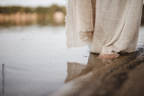 Fotografering Closeup shot of a person wearing a biblical robe walking on the shoreline