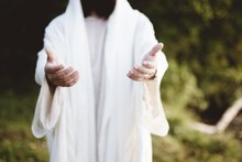 Closeup Of Jesus Christ Reaching Out With A Blurred Background