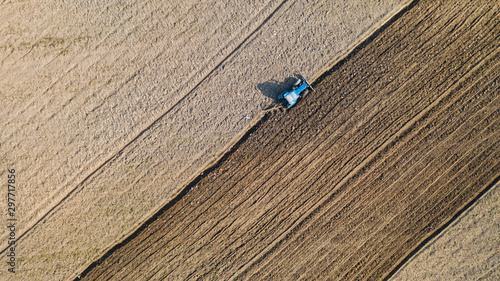 Photo Top view of agricultural tractor vehicles working at field