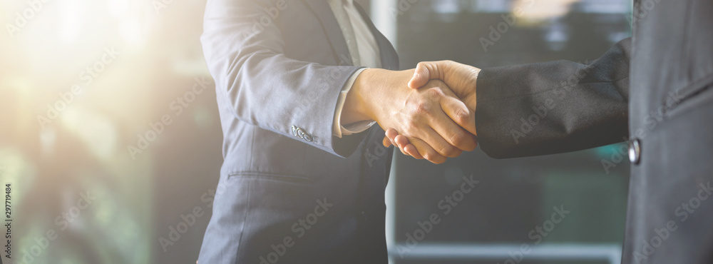 Fototapeta successful negotiate and handshake concept, two businessman shake hand with parthner to celebration partnership and teamwork, business deal