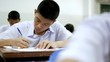 Asian high school students in white uniform are doing examinations.