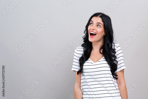 Fotografie, Tablou Surprised young woman posing on a gray background