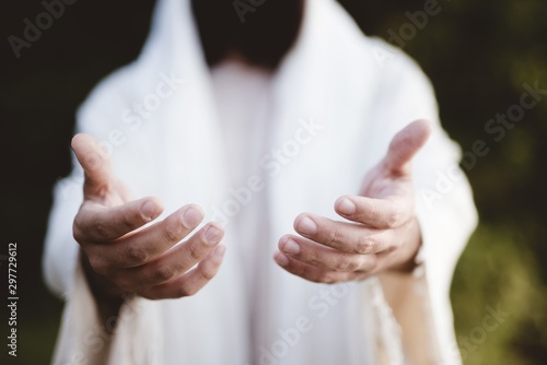 Fotografia Closeup shot of Jesus Christ reaching out with a blurred background